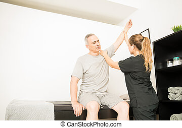 Physical Therapist Lifting Injured Hand Of Patient In Hospital