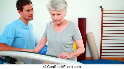 Physical therapist showing patient how to use exercise ...