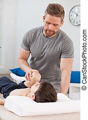 Physical therapist stretching young patient