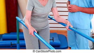 Physical therapist watching patient walk with parallel bars...