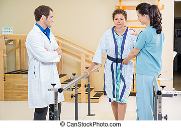 Physical therapist with doctor assisting female patient in walking with the support of bars
