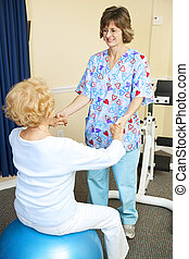 Senior woman exercises with the help of a physical therapist.