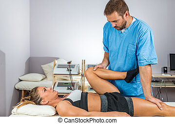 Physical therapy. Therapist working with female athlete