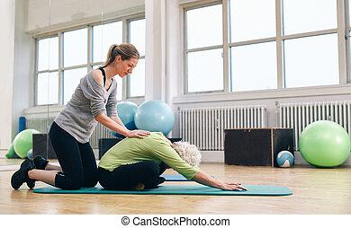 Physical trainer helping elder woman doing yoga