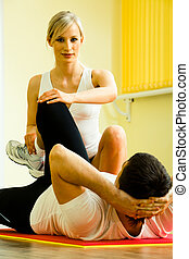 Image of young fitness instructor touching man�s leg while he doing physical exercises