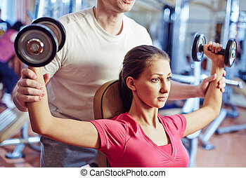 Physical training - Portrait of pretty girl training in gym...