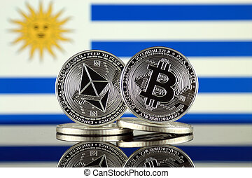 Physical version of Ethereum (ETH), Bitcoin (BTC) and Uruguay Flag. 2 largest cryptocurrencies in terms of market capitalization.