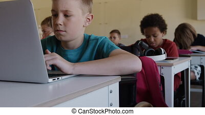 Physically challenged boy using laptop in the class