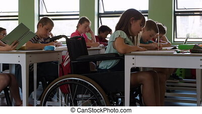 Physically challenged girl writing in her notebook in the class