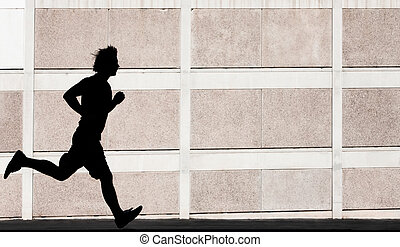 Man in the shadows of building runs for exercise.