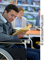 physically handicapped man on wheelchair with books