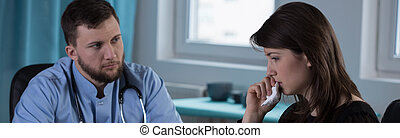Physician and crying widow - Physician giving bad news to...