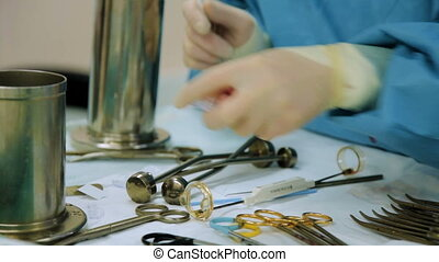 Physician assistant of the surgeon prepares tools for surgery