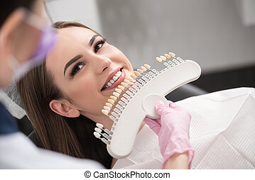 Physician enclosing dental crown to happy lady - Top view...
