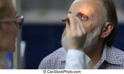 Physician examining pupillary reflex with flashlight -...
