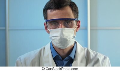 Physician in protective glasses and mask