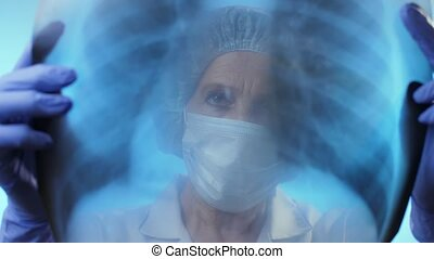 Physician looks at x-ray of the lungs. Coronavirus concept.