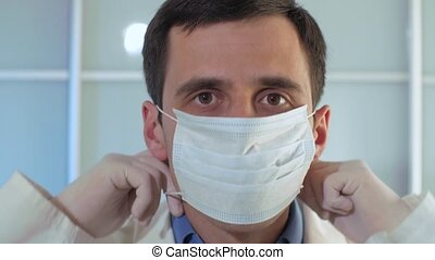 Physician puts on a sterile mask