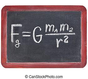 physics education concept - Newton gravity law on a small slate blackboard