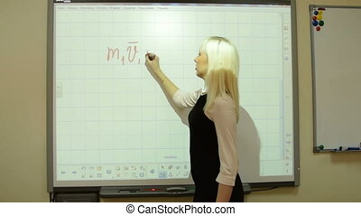 Physics teacher deriving a formula on interactive whiteboard