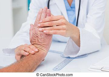 physiotherapeut, patienten, mann, handgelenk, untersuchen