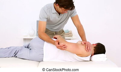 Physiotherapist adjusting patient - Physiotherapist...