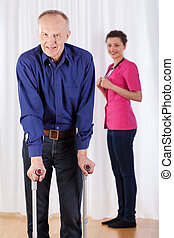 Physiotherapist and  man walking with crutches