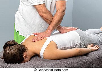 Physiotherapist applying pressure on female spine.