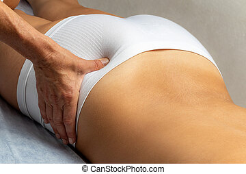 Physiotherapist applying pressure with thumb on female but.