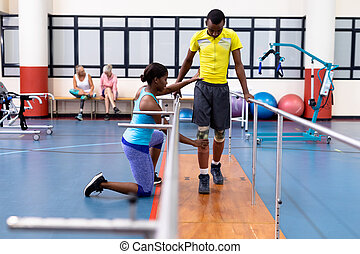 Physiotherapist assisting disabled man walk with parallel bars in sports center