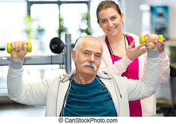 physiotherapist assisting senior man to lift dumbbell in clinic