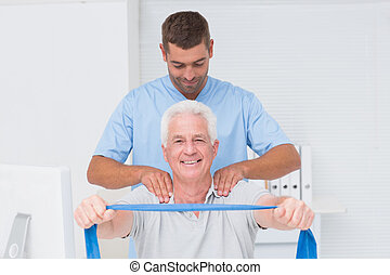 Physiotherapist assisting senior patient in exercising with resi