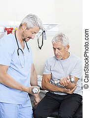 Physiotherapist Assisting Senior Patient In Lifting Dumbbells