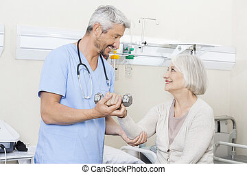 Physiotherapist Assisting Senior Woman To Lift Dumbbells