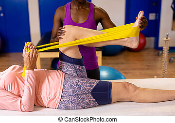 Physiotherapist assisting woman to exercise with resistance ...