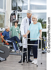 Physiotherapist Assisting Woman With Walker In Fitness Center
