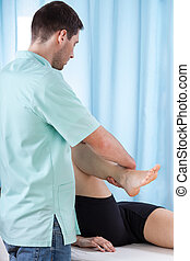 Physiotherapist bending knee of patient lying on treatment...