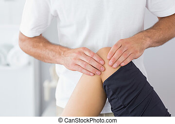 Physiotherapist checking knee of a patient