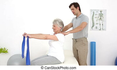 Physiotherapist checking patients shoulder alignment with...
