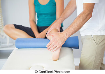 Physiotherapist checking patients leg