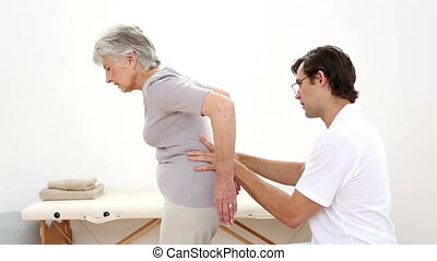 Physiotherapist checking senior patients lower back at the...