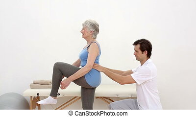 Physiotherapist checking senior patients hip alignment at...
