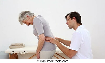 Physiotherapist checking senior patients back at the...