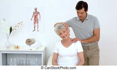 Physiotherapist checking senior patients neck at the...