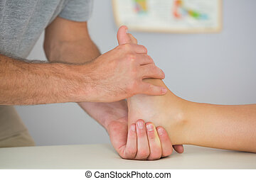 Physiotherapist controlling patients foot in bright office