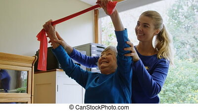 Physiotherapist correcting position of senior woman 4k -...