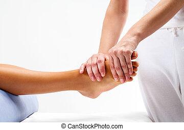 Physiotherapist doing reflexology massage on female foot.