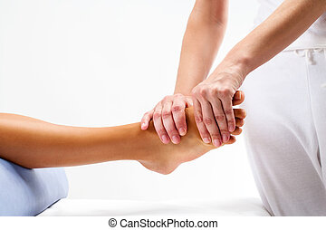 Physiotherapist doing reflexology massage on female foot. -...