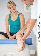 Physiotherapist examining patients leg