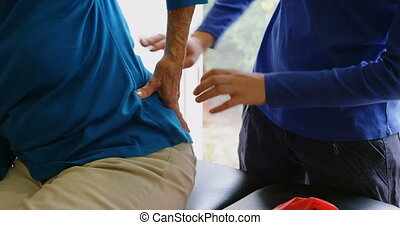Physiotherapist examining senior woman back in clinic 4k -...